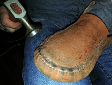 Sømmen blir banket flat / The seam is flattened with a hammer