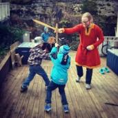 Guttene lekte sverdkamp utenfor huset, og nabogutten gjorde store øyne da en Espen kom ut i vikingklær / Testing the kirtle in combat with the boys and their friend