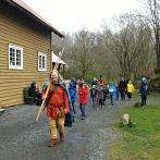 Espen leder an og fører en gruppe med seg på omvisning til fornminnene / Espen guiding a group at the Iron Age monuments