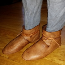 Sigvald prøver de nye støvlene med hosene på / Sigvald trying on his new boots with hoses inside