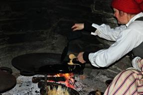 Krumkaker på gammelt jern på takke over åpen ild. Ikke alltid like lett å få jevn varme / It is difficult to get even heat over the open fire