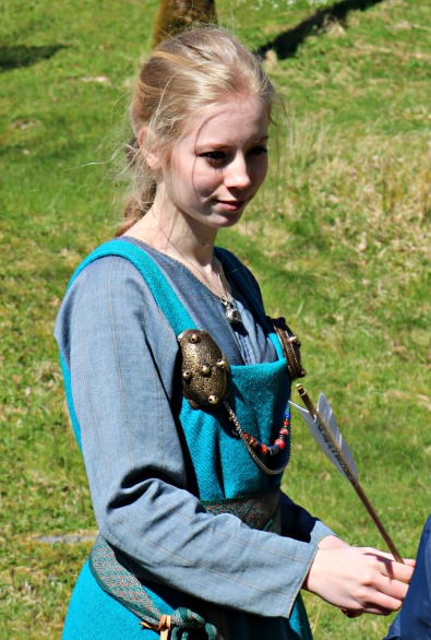 Oline instruerte pil og bue, kledd i vikingtidsdrakt / Oline in charge of bow and arrow, dressed i Viking Age outfit