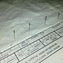 Registreringsskjema fra middelalderinstituttet ble brukt som rutenett for å markere avstand for hjelpesømmen / Using an old registration sheet with squares to place dots i even distances