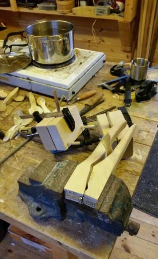 Skjeer i press. I bakgrunnen gryten med horn på kok / Spoons in moulds. In the background the pot where the horn is boiling