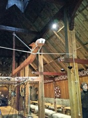 Inne i vikingtids-langhuset. Langhuset brukes bl.a. til formidling, gilder og leirskole / From the interior of the Viking Age long house, a place of feasting and teaching