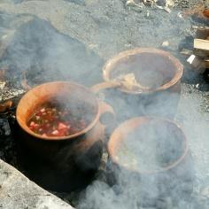 Rotgrønnsaker, bønner og ramsløk med svinekjøtt i to gryter. I andre gryten byggrynsgraut søtet med honning og bær / Stew and porridge in clay pots