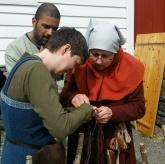 Her viser Julia oss hvordan lage hosebånd. Christian fra Anno var også med på Hordamuseet denne dagen, og han fulgte interessert med / Discussing a special form of braiding