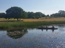 Noen av guttene padler i stokkebåt / Some of the boys in a log boat.
