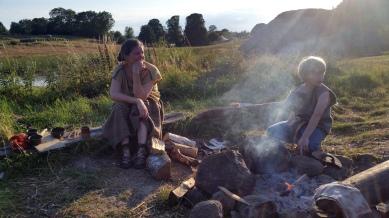 "Lena og Sigvald i landsbyens utekjøkken, altså ved leirbålet / In the village ""kitchen"", more precisely campfire"