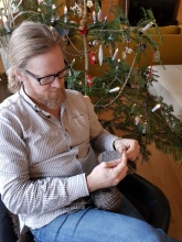 Espen nålebinder votter i godstolen ved juletreet / Needlebinding in the resting chair by the Christmas tree