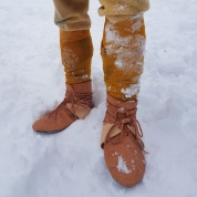 Store sko fylt med gress og hår, med isbrodder utenpå / Large shoes filled with grass and hair, crampons underneath
