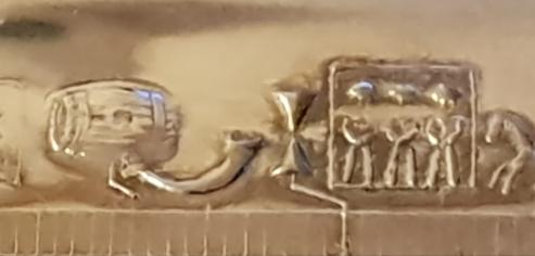 Utsnitt av primstav i metall. Tønnen representerer Thomas Brygger, og drikkehornet er tegnet for juledagen / Calendar in metal. St. Thomas Mass is marked with barrel, Christmas Day with drinking horn