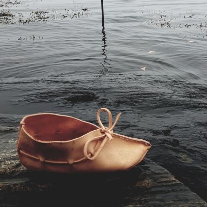 Hudsko og tre lærtriangler i havet / One-piece shoe and three leather wedges in the sea
